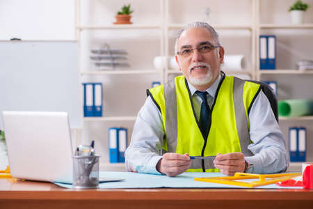 Aged construction engineer working in the office Stock Photo