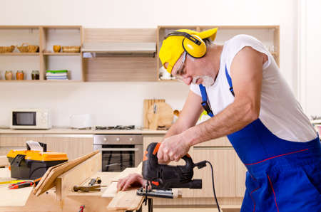 Aged contractor repairman working in the kitchen Reklamní fotografie