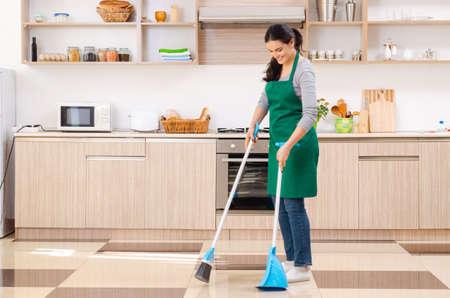 Joven contratista haciendo quehaceres domésticos Foto de archivo
