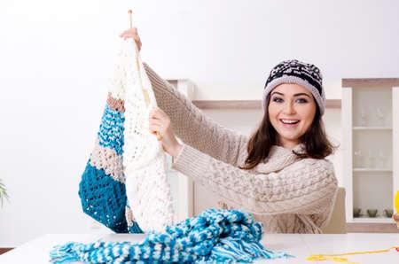 Young beautiful woman knitting at home