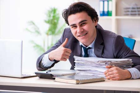 Junger männlicher Angestellter, der im Büro arbeitet