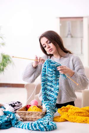 Hermosa joven tejiendo en casa