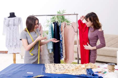 Young beautiful female tailor taking measurements 写真素材