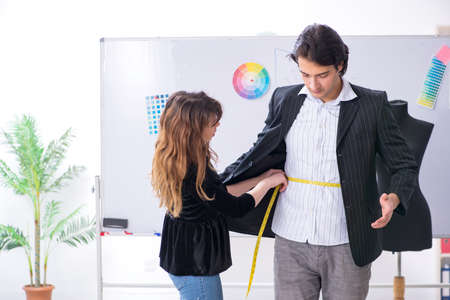 Young female tailor taking measurements for formal suit
