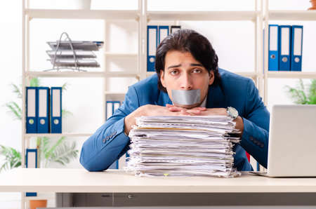 Young male employee with tape on the mouth