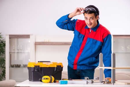 Young contractor repairing furniture at home Stock Photo