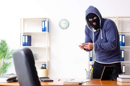 Männlicher Dieb in Sturmhaube im Büro Standard-Bild