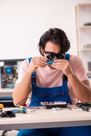 Young male contractor repairing computer Stock Photo