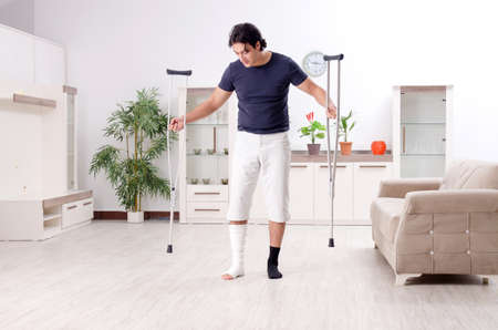 Leg injured young man suffering at home Stock Photo