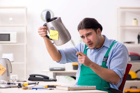 Young man repairing kettle in service centre