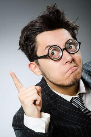 Funny nerd businessman in dark studio Stockfoto