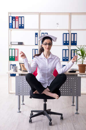 Young female employee doing exercises in the office Stockfoto
