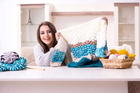 Giovane bella donna che lavora a maglia a casa Archivio Fotografico