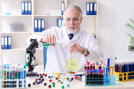 Old male chemist working in the lab