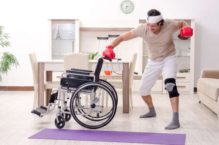 Injured young man doing exercises at home