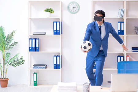 Young handsome businessman playing soccer with virtual glasses