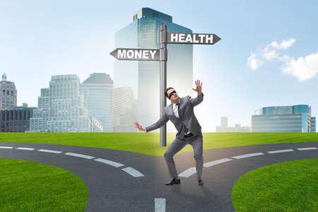 Businessman choosing between money and health Stock Photo