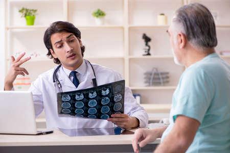Anciano visitando joven médico masculino