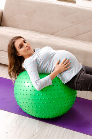 Young pregnant woman doing sport exercises at home Banco de Imagens