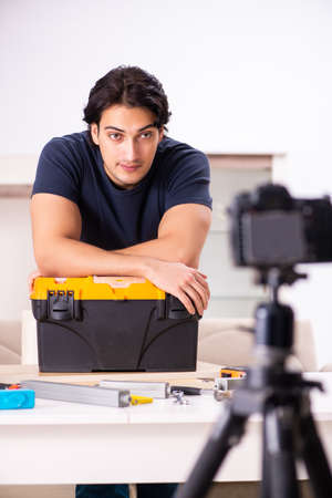 Young male repairman recording video for his blog