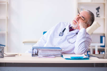 Old male doctor working in the clinic Stockfoto