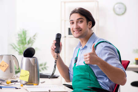 Young man repairing kettle in service centre Stock Photo