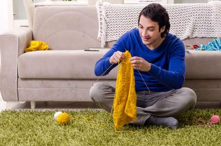 Beau jeune homme tricotant à la maison
