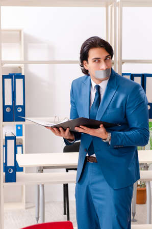Young male employee with tape on the mouth Stockfoto - 124182793