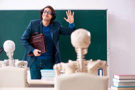 Männlicher Lehrer und Skelettschüler im Klassenzimmer Standard-Bild