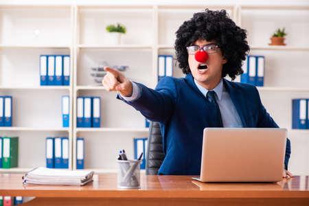 Jeune homme d'affaires de clown travaillant au bureau