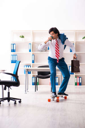 Young handsome businessman with longboard in the office