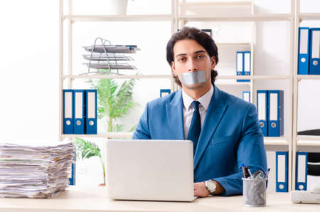 Young male employee with tape on the mouth Stockfoto - 124184617
