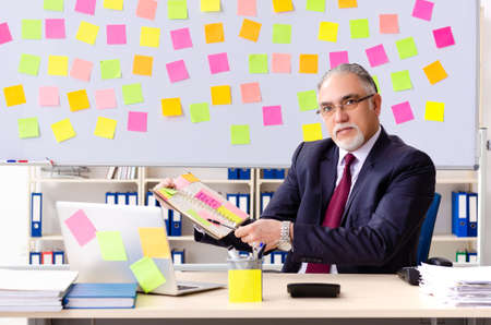 Aged man employee in conflicting priorities concept Stock Photo