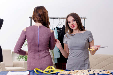 Young beautiful female tailor taking measurements