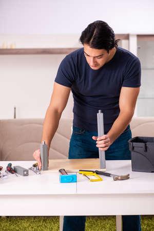 Young man repairing furniture at home