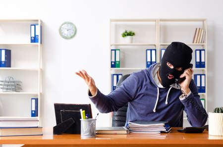 Male thief in balaclava in the office