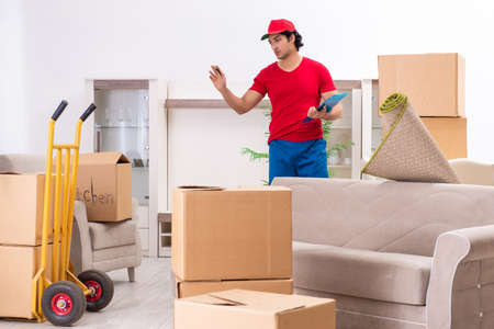 Young male contractor with boxes working indoors Imagens