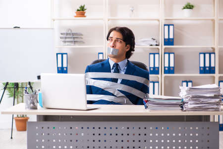 Young tied male employee in the office