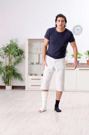 Leg injured young man suffering at home Reklamní fotografie