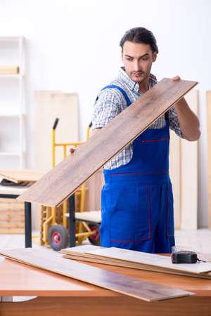 Junger männlicher Tischler, der drinnen arbeitet