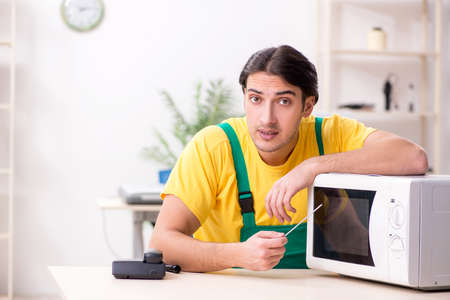 Young repairman repairing microwave in service centre