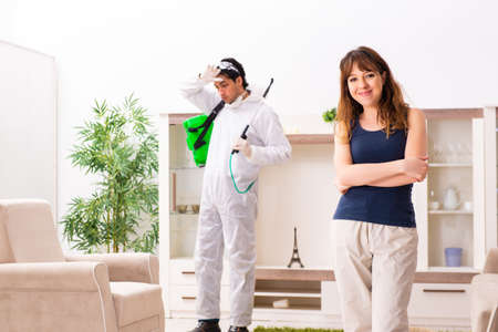 Young professional contractor doing pest control at flat Stock Photo