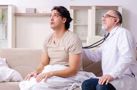 Vieux docteur masculin visitant le jeune patient masculin
