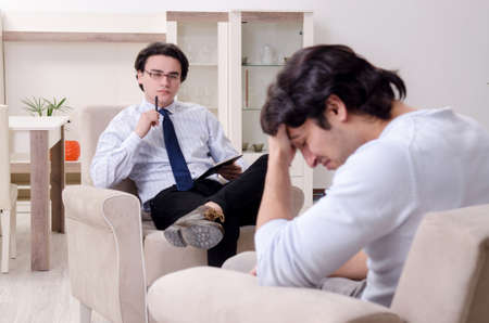 Young male patient discussing with psychologist personal problem