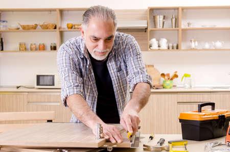 Reparador de contratista de edad trabajando en la cocina