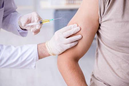 Docteur visitng patient masculin pour l'inoculation de projectile