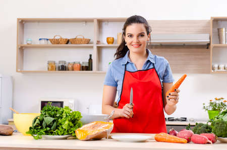 Young woman with vegetables in the kitchen Stock Photo