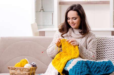 Młoda piękna kobieta robi na drutach w domu