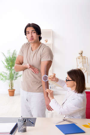 Female doctor checking patients joint flexibility with goniometer