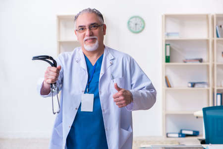 Old male doctor working in the clinic Stock Photo